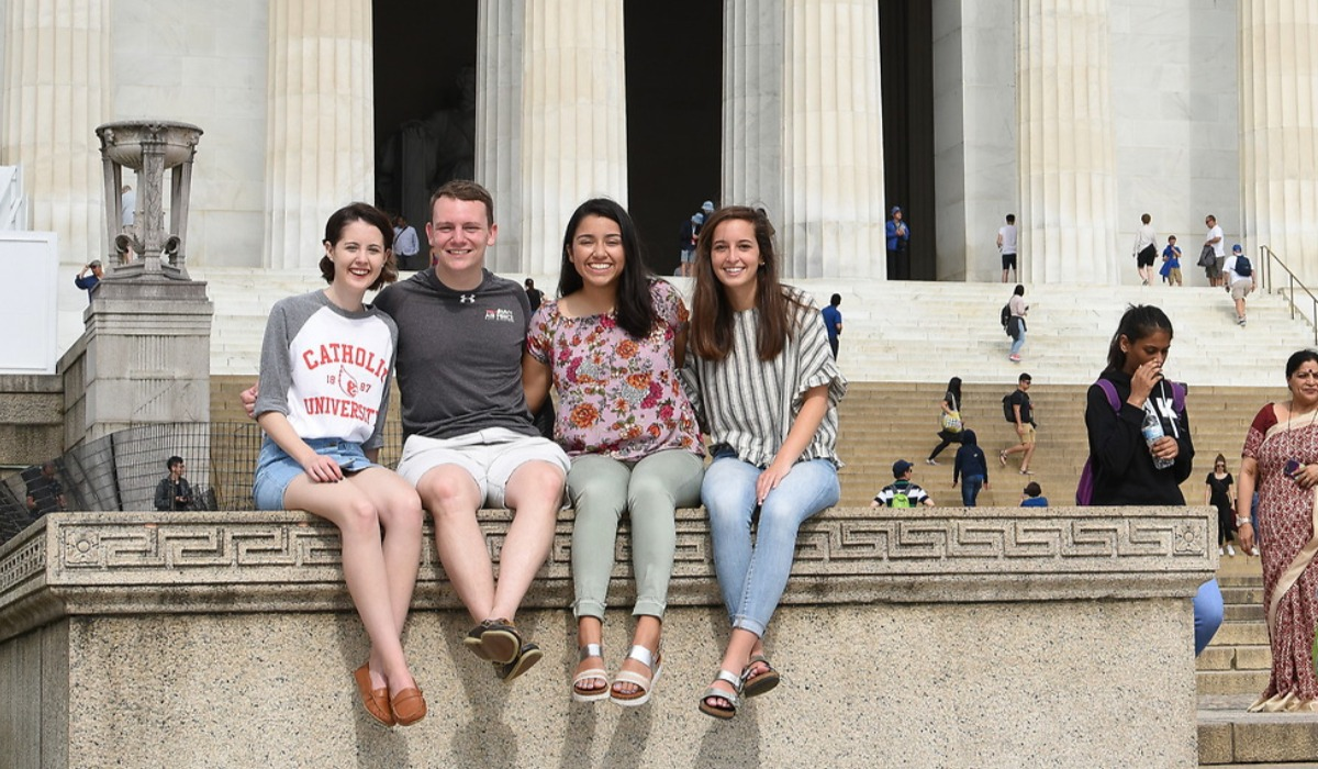 Four students sitting on the Lincoln Memorial