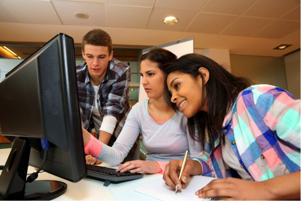 Three students in front of a computer